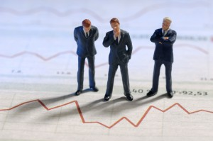 Businesspeople are standing in front of of the graphic of a stock price. ** Note: Shallow depth of field