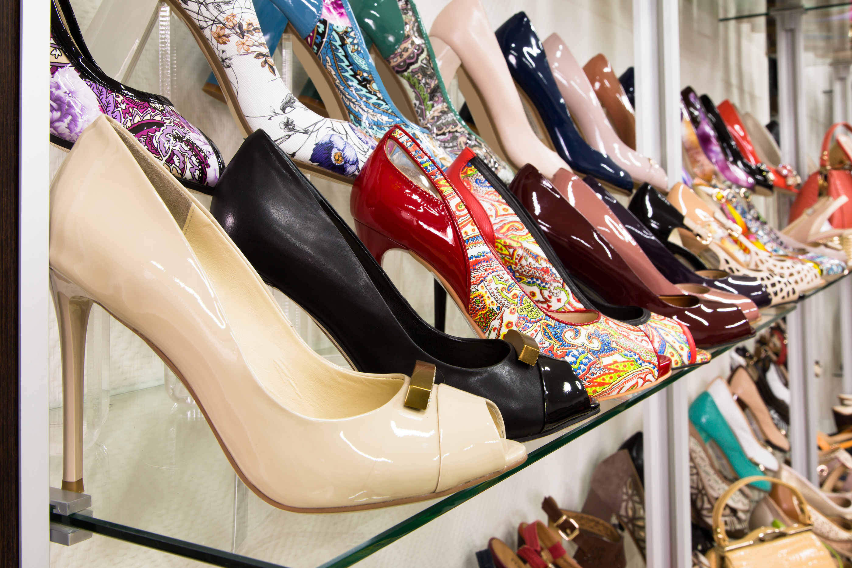 Rows of beautiful elegant colored women's shoes on store shelves.